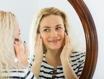 Awake girl looking in mirror on wall Stock Photos