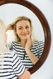 Awake girl looking in mirror on wall Royalty Free Stock Photo