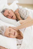 Awake senior woman in bed covering her ears Royalty Free Stock Images