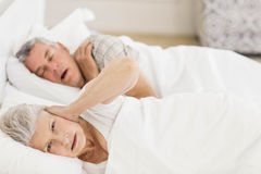 Awake senior woman in bed covering her ears Royalty Free Stock Image
