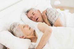Awake senior woman in bed. Awake senior women in bed while her husband is snoring Royalty Free Stock Photography
