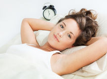 Awake young woman in her bed Stock Photos