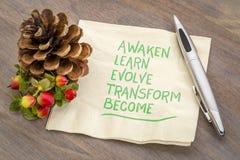 Awaken, learn, evolve, transform, become. Awaken, learn, evolve, transform and become - inspirational words - handwriting on a napkin with a pine cone stock photo