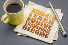 Awaken, learn, evolve, transform, become. Awaken, learn, evolve, transform and become - inspirational word abstract on a napkin with a cup of tea stock photography