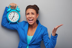 Awaken mixed race woman with alarm clock Stock Image