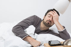 Awakened. Man with beard lying in a bed with white bedding Stock Photo