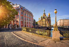 Awakening city. Morning sunny view of the fence of the bridge and the Cathedral of Our Savior on Spilled Blood Stock Images