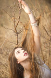 Awakening the earth. Woman rising his hand up in the winter background Stock Image