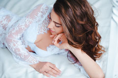 Awakening. Portrait of beautiful young woman with waking up in the morning. Beauty female wearing lingerie in bed Stock Photos