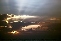 Awakening. Soft spiritual image of sunrise or sunset over tropic. Al sea. Turbulent uncertain weather ahead over the ocean. Change in the weather as clouds form Royalty Free Stock Photo