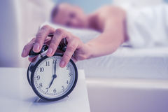 Awaking. Black alarm clock and man royalty free stock photo