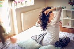 awaking Jonge vrouwenzitting op bed stock fotografie
