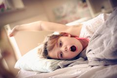 Awaking. Kid in bed. Little girl wake up in bed. Space for copy royalty free stock photos