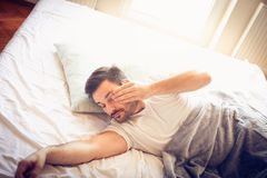 Awaking. Man in bed. From above. stock images