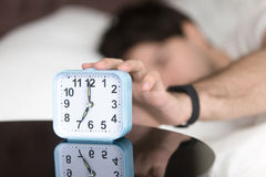 Awaking man in bed wearing wristband turning off alarm clock. Young man sleeping alone is woken by alarm clock signal in the morning. Awaking guy trying to turn royalty free stock photography