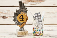 Award and pills on wood. Royalty Free Stock Photography