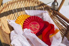 Award ribbon rosettes in horse show and equestrian. Award rosettes for winner in equestrian sport and horse show, red and yellow colors with ribbons in basket Royalty Free Stock Photography