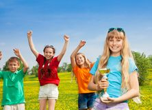 Award for winner. Happy blond girl with prize cup award with her friends jumping on background stock images