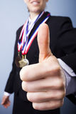 Award winning businesswoman giving thumbs up. Selective focus on an award winning businesswoman giving thumbs up Stock Photography