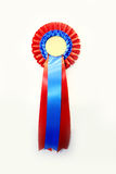 Award winning rosette on full white background. Red and blue colored blank award ribbon rosette for winners Stock Photo