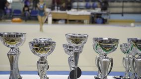 Awards cups, Rhythmic gymnastics, blurred athlete performance in the background stock footage