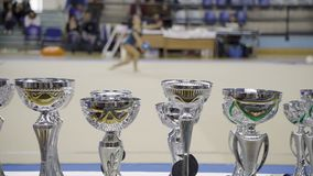 Awards cups, Rhythmic gymnastics, blurred athlete performance in the background stock video footage