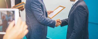 Awards a diploma of another man at a business meeting. Awards a diploma at a business meeting Royalty Free Stock Image