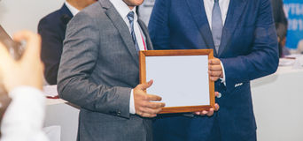 Awards a diploma of another man at a business meeting. Awards a diploma at a business meeting Royalty Free Stock Images