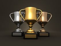 Awards - gold, silver and bronze trophies. Awards on dark studio background - gold, silver and bronze trophies Stock Photography