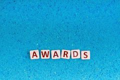 Awards word on stone. Awards word write in square white stone on blue sand, free space for your text Royalty Free Stock Photography
