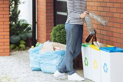 Aware person segregating household waste. Close-up of aware person segregating household waste on the terrace stock photography