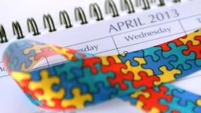 Awareness ribbon falling on calendar marking awareness day Royalty Free Stock Image