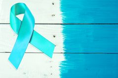 Awareness ribbon of Green on wooden background. PTSD of Posttra royalty free stock photography