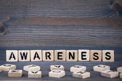 Awareness word written on wood block. Dark wood background with texture Royalty Free Stock Images
