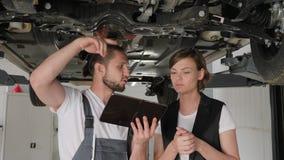 Awaria pojazd, kobieta samochód łamający, samochodowa ` s usługa pracownika rozmowa z klientem, mistrz pokazuje technicznego waru zbiory wideo