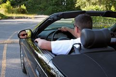 Away we Go. A young man driving away in his shiny black convertible stock image