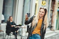away kaffetake Härlig ung stads- kvinna som bär i svart stilfull kläder som rymmer kaffekoppen och ler, medan promenera Arkivbild