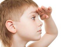 away pojke som ser långt fast beslutsamt Arkivbild