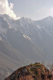 Awe Inspiring Grandeur, Meditation, Sangla Valley, India. A tiny speck of a person meditates before the immense Himalayas, outside of a small tibetan style Stock Image