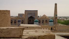 An awe inspiring view of a mosaic temple complex. A wide, still shot view of the awe inspiring mosaic temple complex in Xiva, Uzbekistan, with decorated towers stock video