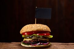 Classic American cheeseburger with black flag on the top over dark background, close-up, selective focus. Awersome classic American cheeseburger with lettuce Stock Image