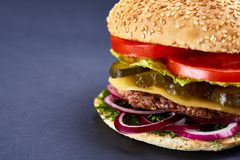 Classic American cheeseburger with black flag on the top over dark background, close-up, selective focus. Awersome classic American cheeseburger with lettuce Stock Photos