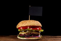 Classic American cheeseburger with black flag on the top over dark background, close-up, selective focus. Awersome classic American cheeseburger with lettuce Stock Photo