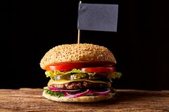 Classic American cheeseburger with black flag on the top over dark background, close-up, selective focus. Awersome classic American cheeseburger with lettuce Stock Photography