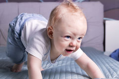 Awesome baby boy trying to do first steps. Cute infant kid crawling on the bed stock photos