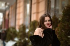 Awesome brunette woman wearing warm coat and posing near the spr. Awesome young woman wearing warm coat and posing near the spruce with snow Stock Photo