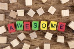 Awesome. Concept: Awesome, colorful plastc toy letters on wooden cubes stock images