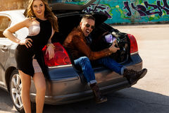 Awesome couple enjoys bag full of money in trunk of car Royalty Free Stock Photo