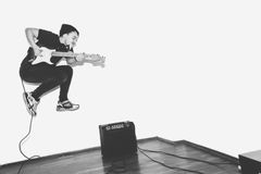 Awesome crazy fashion young musician rock guitar player jumps with passion in studio. Stylish rocky emotional man. Black Royalty Free Stock Images