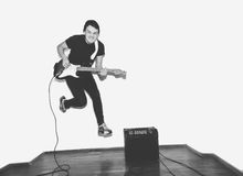 Awesome crazy fashion young musician rock guitar player jumps with passion in studio. Stylish rocky emotional man. Black Stock Photos